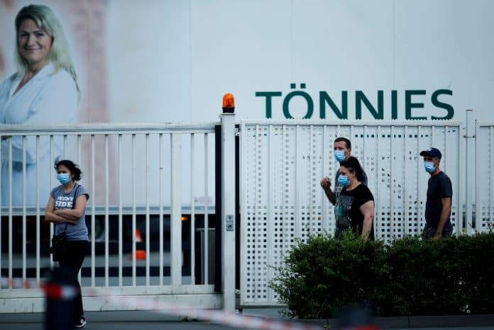 Employees are seen outside the main Tönnies meat factory that had to be shut down because of the coronavirus disease outbreak