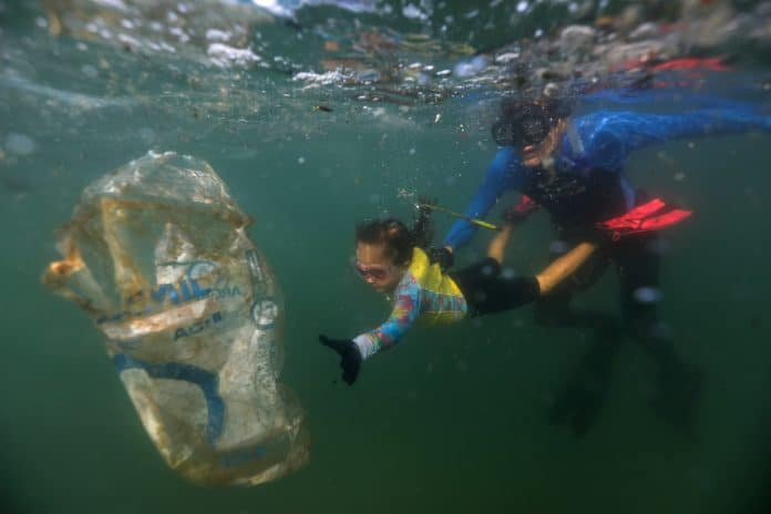 Nina reaches for a plastic bag in the ocean, she's wearing pink goggles with her dad right behind her