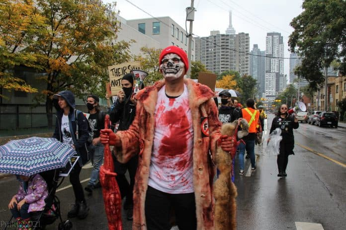 Man wears a face mask fully covered in blood wearing a fur coat and holding two dead animals